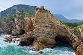 stock photo of frazzled  - sea cave and rocks on coastline of beach of sea - JPG