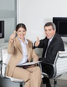Two happy business people in the office holding their thumbs up