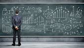 image of clever  - Business person standing against the blackboard with a lot of data written on it - JPG