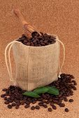 Coffee beans in a hessian drawstring sack and loose with leaf sprigs and olive wood scoop over cork