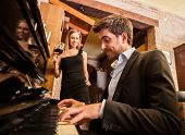 stock photo of serenade  - Man playing piano for his girlfriend - JPG