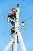 picture of lineman  - Electrician lineman repairman worker at climbing work on electric post power pole - JPG