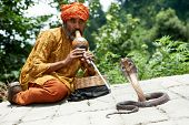 stock photo of serpent  - Indian Snake charmer adult man in turban playing on musical instrument before snake at a basket - JPG