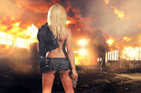 stock photo of gunshot  - special tactics sexy woman holding up her weapon with explosion behind her - JPG