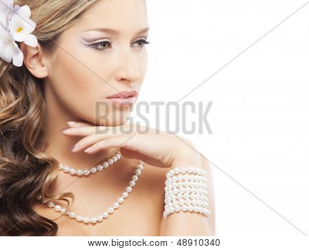 Young and attractive lady with a pearl jewelry and a flower in her hair over white background