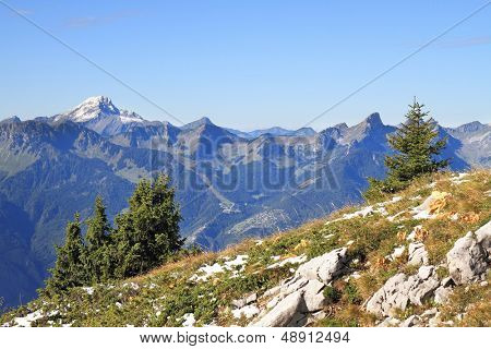 The magnificent Swiss Alps in an early autumn. Green Alpine meadows adjoin to the first easy snow