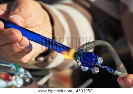 Heikle Arbeit des Gebläses Glas. Auf einem Foto sind die Hände des Meisters sichtbar. Der Künstler-Glas-Schlag