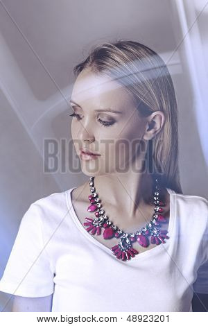 Portrait of a beautiful young blond woman wearing fashion statement necklace over white t-shirt on studio background with light effect
