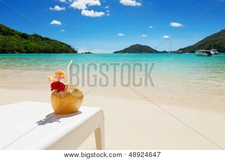 Tropical Cocktail In Coconut Shell With Red Hibiscus Flower, On White Beach Chair, With Perfect Blue