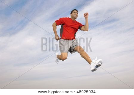 Low angle of a male athlete running midair against the sky and clouds