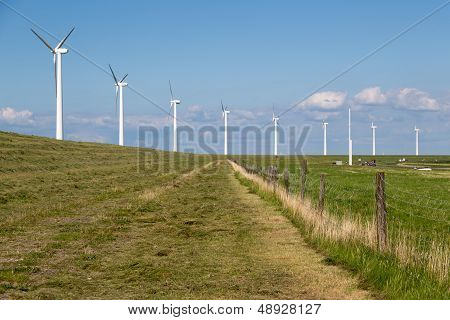 Windturbines Along A Dike In The Netherlands Near A Motorway