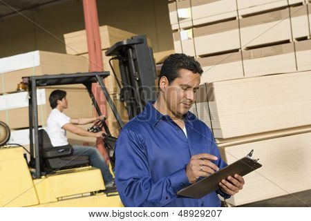 Male supervisor with clipboard and forklift truck driver in the background