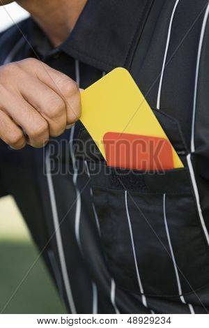 Closeup midsection of a referee taking card from his pocket