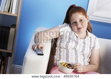 Portrait of a smiling overweight girl with remote control eats junk food on the couch