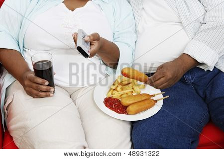 Closeup midsection of an overweight couple with junk food holding remote control