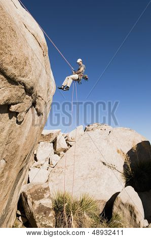 Low angle view of a young man rappelling from cliff against clear blue sky