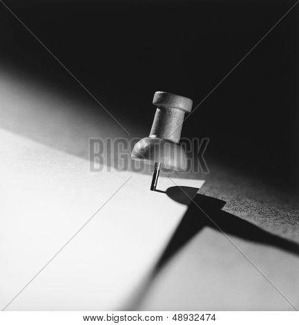 Push pin holding down paper (b&w) (close-up)