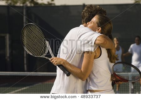 Tennis Players holding rackets Hugging at Net side view