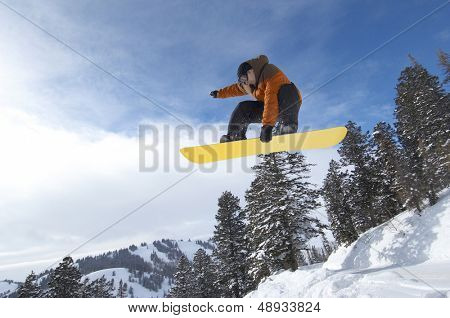 Low angle view of a male snowboarder jumping over snow covered hill against the sky