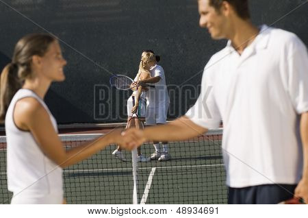 Tennis players shaking hands at net with teammates hugging in background