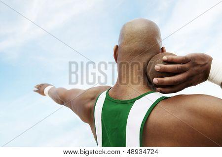 Vista traseira closeup de uma arremessadora de peso se preparando para lançar o arremesso contra o céu