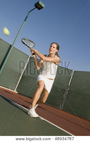 Full length of a female tennis player hitting backhand on the tennis court