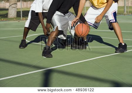 Low section of three men playing basketball