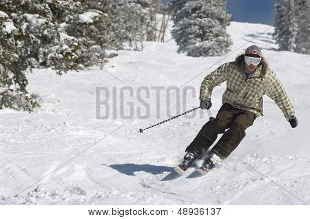 Full length of a young man skiing down snow covered slope