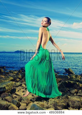 Beautiful lady in a green dress on a rocky shore