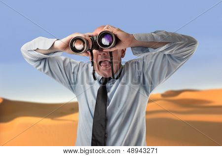 astonished businessman looking with binoculars in the desert