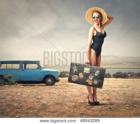 beautiful woman with bathing suit, straw hat and vintage suitcase