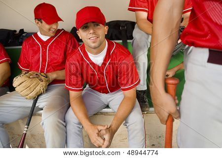 Portrait of a baseball player with team mates sitting in the dugout