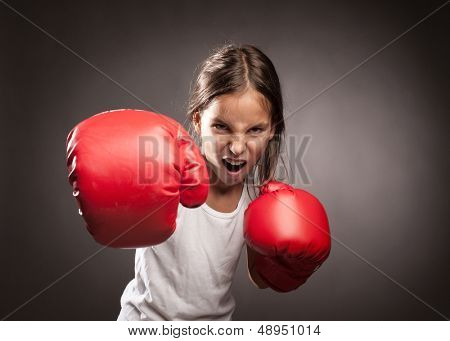 little girl wearing red boxing gloves