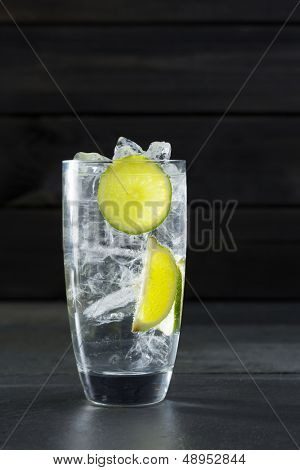 Gin tonic cocktail with lima and ice cube on black slate stone background
