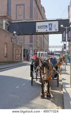 DUBLIN, IRELAND - JUNE 7: Horse drawn carriages wait for tourists in front of Guinness Storehouse, Dublin, Ireland on June 7, 2013