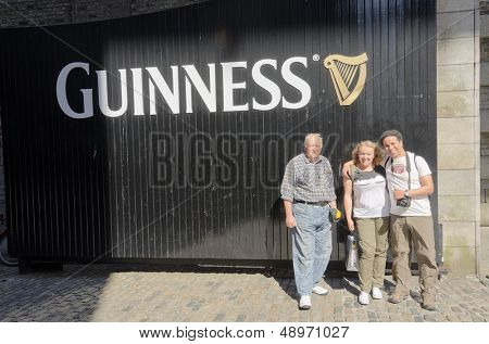 DUBLIN, IRELAND - JUNE 7: Tourists' family posing in front of Guinness logo in Guinness Storehouse, Dublin, Ireland on June 7, 2013
