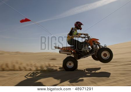 Side view of a quad bike rider doing wheelie in desert against the sky
