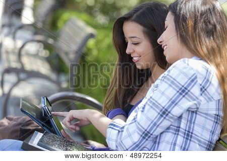 Two Happy Mixed Race Students Using Touch Pad Computer Outside Together on Campus.