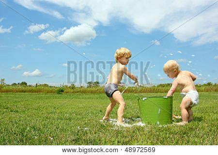 Children Playing With Bucket Of Bubbles