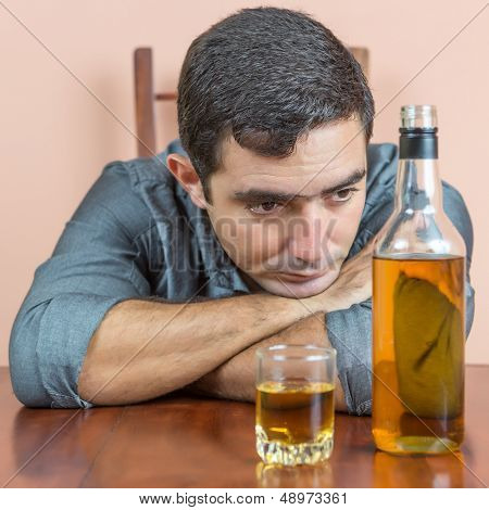Drunk and depressed hispanic  man with an alcoholic liquor bottle and a glass containing whisky or rum