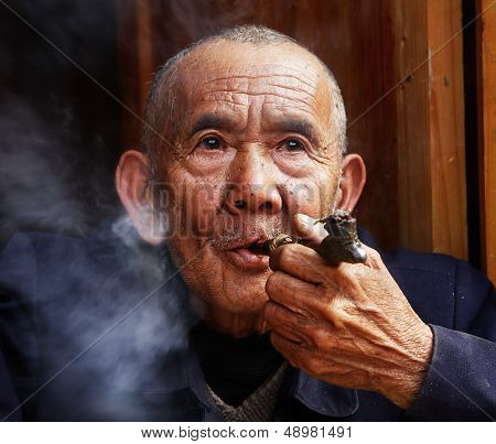 The Chinese Peasant Smokes A Tube Front Of His House.  Aged Chinaman Lit His Handset And Let Tobacco