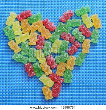 gummy bears of different colors forming a heart on a blue woven background