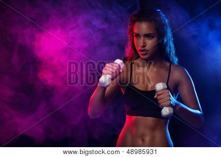 Determined fit sexy woman working out with dumbells on blue and violet smoky wave background