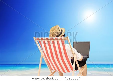 Young man on an outdoor chair working on a laptop, on a beach next to a sea