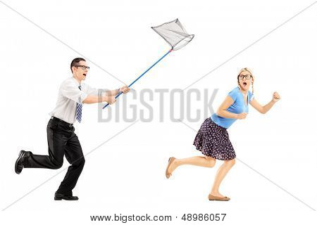 Full length portrait of a scared young female trying to runaway from man with butterfly net isolated on white background