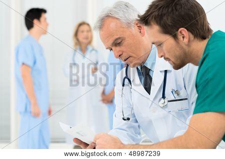 Grupo de médicos involucrados en discusiones serias con registros médicos