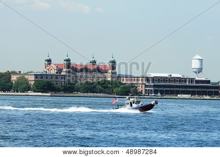 NYPD boat patrolling New York Harbor in the front of Ellis Island