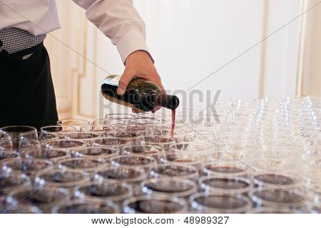 Waiter pouring red wine into many glasses