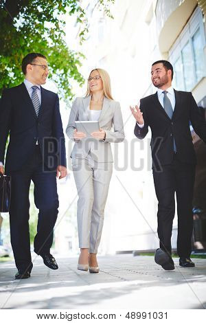 Vertical image of three business partners talking while walking down modern street
