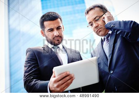 White-collar workers discussing business project in touchpad and consulting via mobile phone